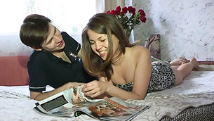 Beautiful girl is lying on the and reading a magazine with her boyfriend
