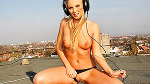 Seductive half naked blonde is dancing on the roof top with her headphones