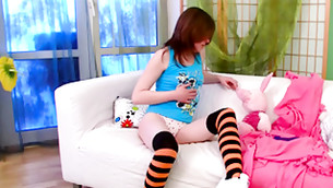 Horny chick in tights sitting on a bed and playing with a toy
